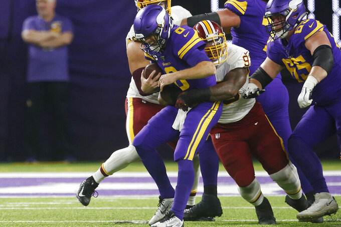 FILE - In this Oct. 24, 2019, file photo, Minnesota Vikings quarterback Kirk Cousins (8) is sacked by Washington Redskins defensive end Jonathan Allen (93) during the first half of an NFL football game in Minneapolis. The Washington Redskins have exercised the fifth-year option on defensive lineman Jonathan Allen's rookie contract. The team announced the expected move Monday, April 27, 2020, in the aftermath of the NFL draft. (AP Photo/Jim Mone, File)