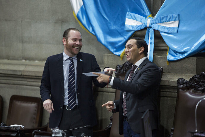 Guatemalan Congress President, Alvaro Arzu Escobar, left, has a laugh with congressman Juan Manuel Giordano during a session of Congress in Guatemala City, Wednesday, Dec. 11, 2019. Guatemala's congress is leading their own investigative commission against the U.N.-sponsored anti-graft commission that over the course of 12 years helped bring to justice hundreds of politicians, businesspeople, judges and others accused of corruption. (AP Photo/Oliver de Ros)