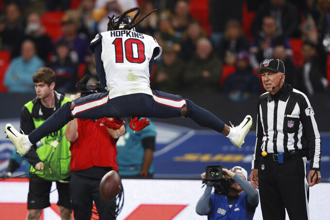 Houston Texans wide receiver DeAndre Hopkins (10) celebrates his touchdown as side judge Joe Larrew (73) looks on against the Jacksonville Jaguars during the second half of an NFL football game at Wembley Stadium, Sunday, Nov. 3, 2019, in London. (AP Photo/Ian Walton)
