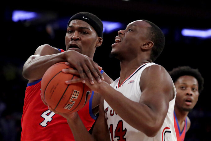 St. John's guard Mustapha Heron (14) tries for a shot against DePaul forward Paul Reed (4) during the first half of an NCAA college basketball game in the Big East men's tournament, Wednesday, March 13, 2019, in New York. (AP Photo/Julio Cortez)