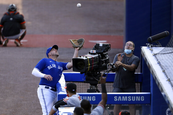 Toronto Blue Jays first baseman Travis Shaw, left, catches a foul ball hit by a Baltimore Orioles batter during the sixth inning of a baseball game, Sunday, Sept. 27, 2020, in Buffalo, N.Y. (AP Photo/Jeffrey T. Barnes)