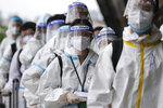 Foreign passengers wearing protective suits line up for their flight to China at Manila's International Airport, Philippines, Monday, Jan. 18, 2021. Coronavirus infections in the Philippines have surged past 500,000 in a new bleak milestone with the government facing criticisms for failing to immediately launch a vaccination program amid a global scramble for COVID-19 vaccines. (AP Photo/Aaron Favila)