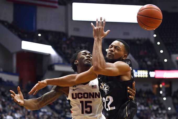 Connecticut's Sidney Wilson (15) loses the ball as he tangles with Central Florida's Darin Green Jr.(22) in the first half of an NCAA college basketball game, Wednesday, Feb. 26, 2020, in Hartford, Conn. (AP Photo/Jessica Hill)