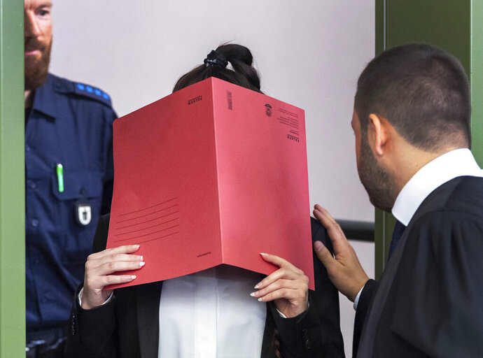 27-year-old German Jennifer W. covers her face as she arrives at a court in Munich, southern Germany, Tuesday, April 9, 2019. The woman is accused of letting a 5-year-old girl she and her husband held as a slave in Islamic State-held territory in Iraq die of thirst. (Peter Kneffel/dpa via AP)