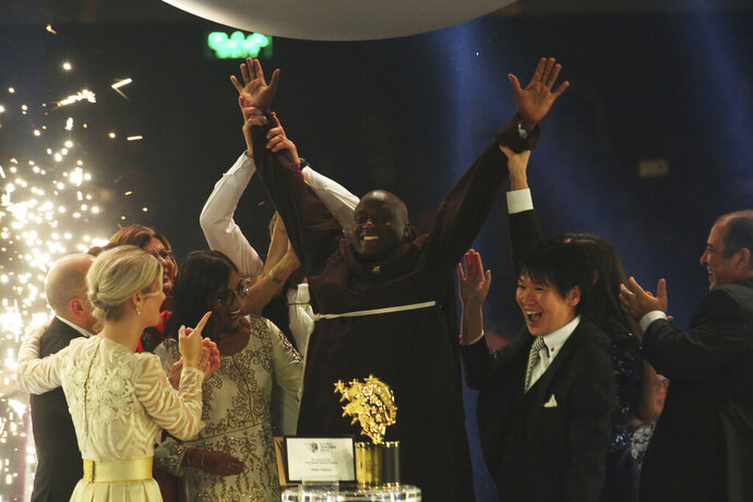 Kenyan teacher Peter Tabichi, center, reacts after winning the $1 million Global Teacher Prize in Dubai, United Arab Emirates, Sunday, March 24, 2019. Tabichi is a science teacher who gives away 80 percent of his income to the poor in the remote Kenyan village of Pwani. (AP Photo/Jon Gambrell)