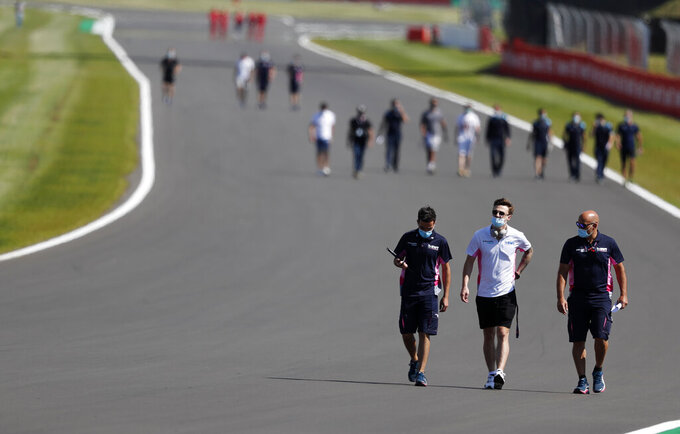 F1 drive hrs walk along the track with team members ahead of the British Formula One Grand Prix at Silverstone circuit, Silverstone, England, Thursday, July 30, 2020.(AP Photo/Frank Augstein)