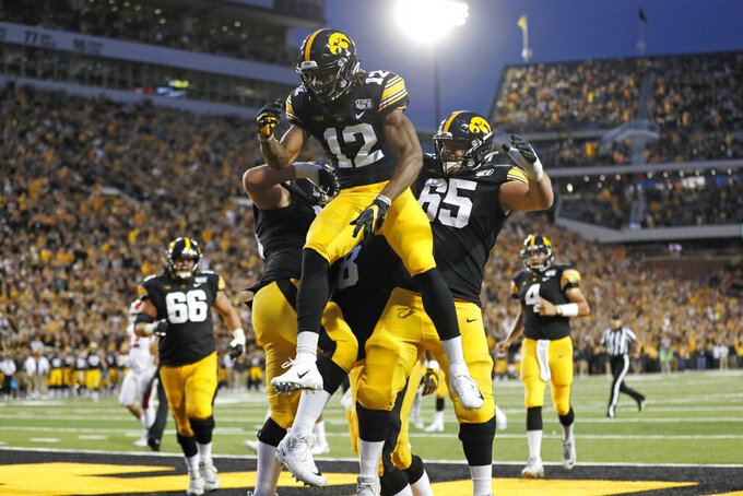 Iowa wide receiver Brandon Smith (12) celebrates with teammates after catching a touchdown pass during the first half of an NCAA college football game against Miami of Ohio, Saturday, Aug. 31, 2019, in Iowa City, Iowa. (AP Photo/Charlie Neibergall)