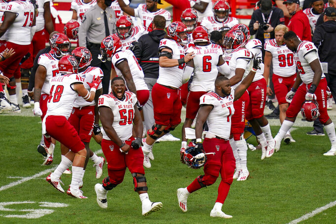 The North Carolina State defense celebrates as time runs out, defeating the No. 24 Pittsburgh in an NCAA college football game, Saturday, Oct. 3, 2020, in Pittsburgh. North Carolina State won 30-29. (AP Photo/Keith Srakocic)