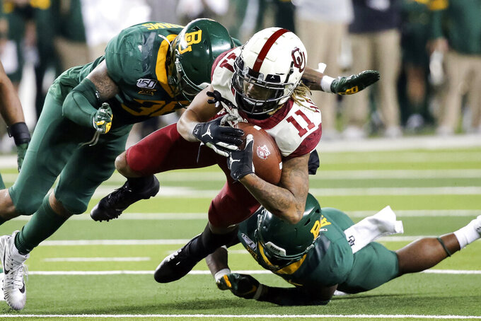 Baylor linebacker Jordan Williams, left, and Baylor cornerback Grayland Arnold, right, make the tackle on Oklahoma wide receiver Jadon Haselwood, center, during the second half of an NCAA college football game in Waco, Texas, Saturday, Nov. 16, 2019. Oklahoma won 34-31. (AP Photo/Ray Carlin)