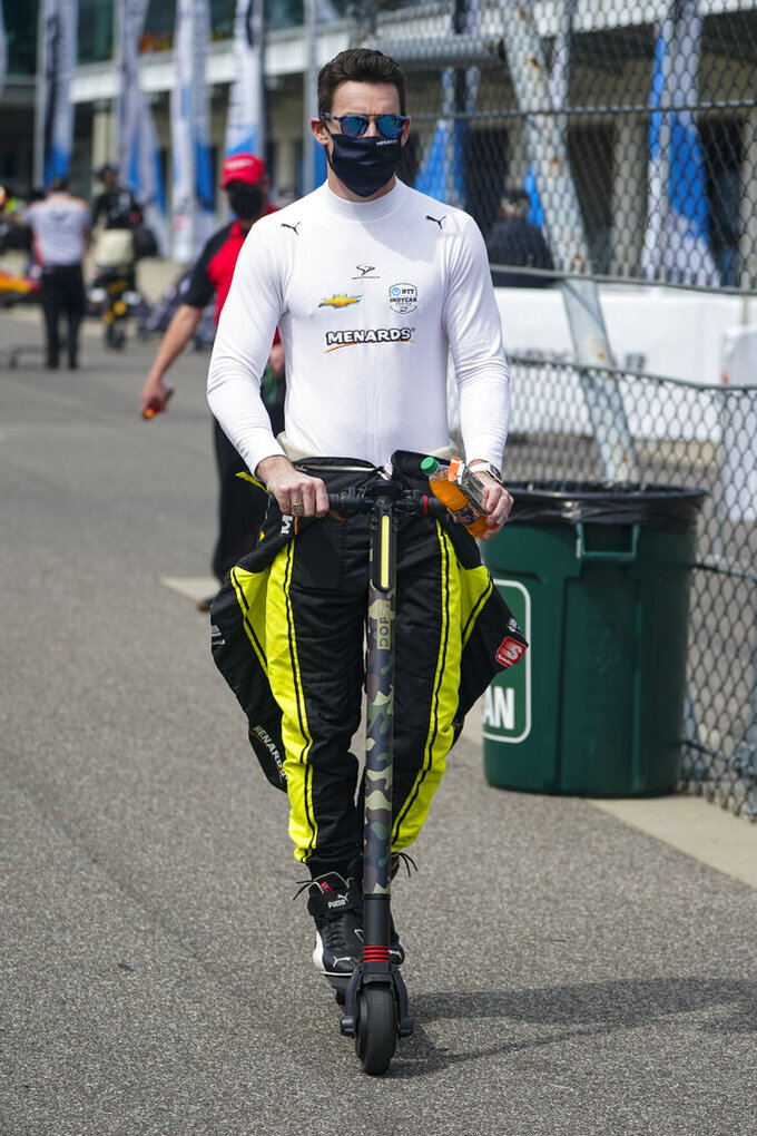 Simon Pagenaud of France rides a scooter through the pit area during practice for the Indianapolis 500 auto race at Indianapolis Motor Speedway in Indianapolis, Tuesday, May 18, 2021. (AP Photo/Michael Conroy)