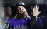 Colorado Rockies' Charlie Blackmon is congratulated by teammates as he returns to the dugout after hitting a solo home run off San Diego Padres relief pitcher Gerardo Reyes during the sixth inning of a baseball game Thursday, June 13, 2019, in Denver. (AP Photo/David Zalubowski)