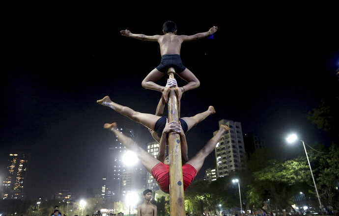 In this Feb. 6, 2019, photo, players perform on a mallakhamb pole at the Shree Samartha Vyayam Mandir at Shivaji Park in Mumbai, India. The word mallakhamb comes from malla, meaning wrestler, and khamb, or pole, and is a traditional training exercise for wrestlers in India. After centuries of being practiced in isolation in the subcontinent, mallakhamb is set to have its first international championship in Mumbai on Feb. 16 and 17. (AP Photo/Rafiq Maqbool)