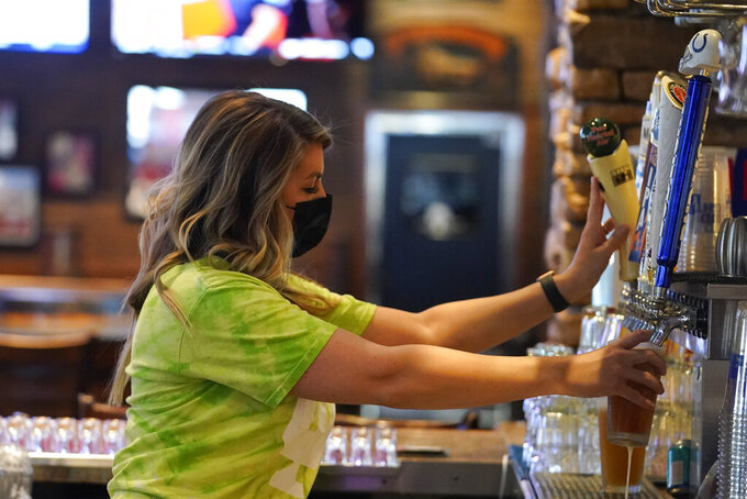 Jillian Smith pours a beer for a customer at Kilroy's Bar & Grill, Sunday, March 14, 2021, in Indianapolis. The NCAA Tournament and bars were made for each other, with fans of powerhouse teams like Gonzaga and longshots like Colgate pouring in to cheer their teams. Until last year, that is, when COVID-19 blew up everybody's brackets. This year, the tournament's back, and bars and restaurants, some shuttered for months, are open for March Madness, though things may look a little different.(AP Photo/Darron Cummings)