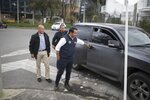 """Wilson Florez, candidate of Democratic Center political party for the government of Cundinamarca, disembarks from his armored SUV, accompanied by his bodyguard, in Bogota, Colombia, Wednesday, Oct. 23, 2019. When Florez learned of a threatening pamphlet circulating in a small town outside Bogota's office where he'd campaigned, he said authorities responded by equipping him with a bulletproof vest and a """"self-protection guide."""" (AP Photo /Ivan Valencia)"""