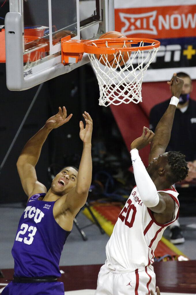 Oklahoma's Rick Issanza (20) blocks a shot by TCU's Jaedon Ledee (23) during the second half of an NCAA college basketball game in Norman, Okla., Tuesday, Jan. 12, 2021. (AP Photo/Garett Fisbeck)