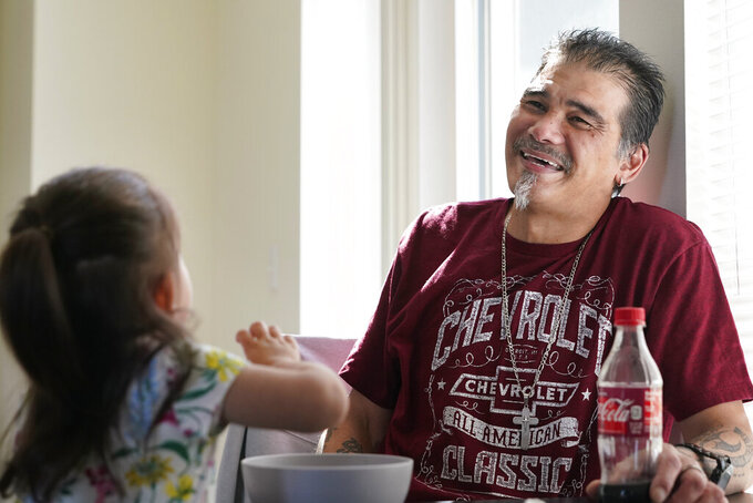 Leroy Pascubillo smiles as he looks at his daughter, who was born addicted to heroin and placed with a foster family at birth, and talks about his journey regaining custody, May 10, 2021, in Seattle. Pascubillo, who had used drugs for the better part of four decades, was in a court-ordered in-patient drug rehab program when the pandemic first hit. (AP Photo/Elaine Thompson)