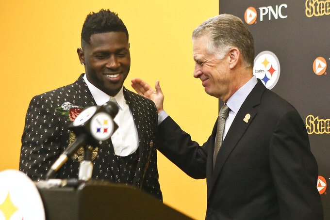 FILE - In this Feb. 28, 2017, file photo, Pittsburgh Steelers wide receiver Antonio Brown, left, smiles as he is introduced by Steelers President Art Rooney II for a news conference about Brown's contract extension at the NFL football team's headquarters, Tuesday, Feb. 28, 2017, in Pittsburgh. Steelers wide receiver Antonio Brown has ended his lengthy standoff with the team by meeting with president Art Rooney II, though any shot at reconciliation between the two sides appears to be out of the question. Brown, who has asked to be traded, posted a picture on various social media accounts on Tuesday, Feb. 19, 2019,  that showed him arm in arm with Rooney at the Palm Beach International Airport. (AP Photo/Keith Srakocic, File)