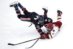 Northeastern forward Brandon Hawkins, left, and Boston College defenseman Michael Kim, right, collide as they chase the puck during the first period of the NCAA hockey Beanpot tournament championship game in Boston, Monday, Feb. 11, 2019. (AP Photo/Charles Krupa)