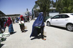 Afghans receive free food donated by King Salman Humanitarian Aid and Relief Center, ahead of the upcoming holy fasting month of Ramadan in Kabul, Afghanistan, Sunday, May 5, 2019. Muslims throughout the world are celebrating the holy fasting month of Ramadan, refraining from eating, drinking, and other pleasures from sunrise to sunset. (AP Photo/Rahmat Gul)