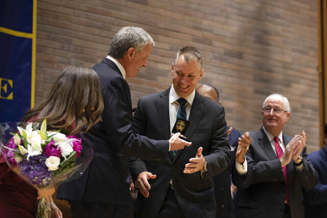 Mayor Bill de Blasio, second from left, presents the commissioner's badge to Police Commissioner Dermot Shea with at police headquarters Monday, Dec. 2, 2019, in New York. . (AP Photo/Kevin Hagen).