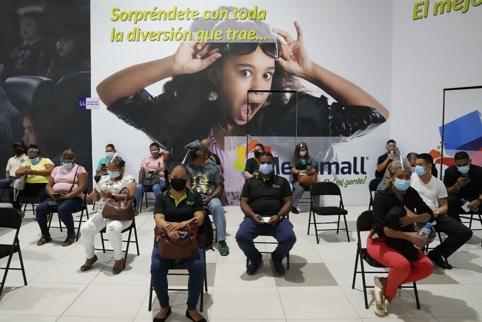 Residents sit in observation after getting shots of the AstraZeneca vaccine for COVID-19 at Mega Mall on the outskirts of Panama City, Wednesday, June 9, 2021. (AP Photo/Arnulfo Franco)