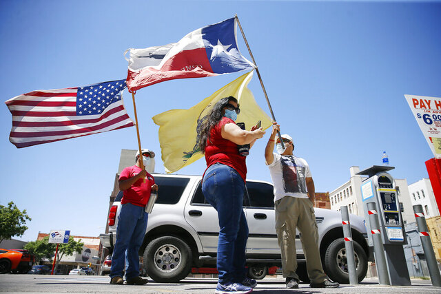 Protesters attend a Safely Open Texas Now rally Saturday, April 25, 2020, across the street from the El Paso County Court House in El Paso, Texas, during the coronavirus outbreak. The protesters demanded elected officials safely reopen the State of Texas, the County of El Paso and the city of El Paso for business. (Briana Sanchez/The El Paso Times via AP)
