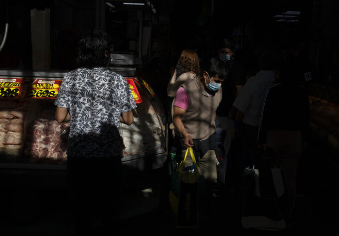 People shop at the La Vega market in Santiago, Chile, Saturday, June 12, 2021, amid the new coronavirus pandemic. The Chilean capitol has reinstated quarantine measures due to the increase in COVID-19 infections. (AP Photo/Esteban Felix)