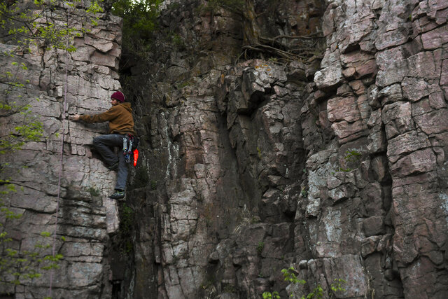 Cody Wiseman climbs his way to the top of a rock formation on Thursday, May 14, 2020 at Palisades State Park in Garretson, S.D. (Abigail Dollins/The Argus Leader via AP)
