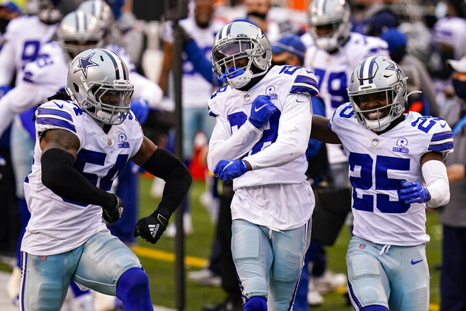 Dallas Cowboys cornerback Rashard Robinson, center celebrates a defensive stop against the Cincinnati Bengals with free safety Xavier Woods (25) and middle linebacker Jaylon Smith (54) in the second half of an NFL football game in Cincinnati, Sunday, Dec. 13, 2020. (AP Photo/Bryan Woolston)
