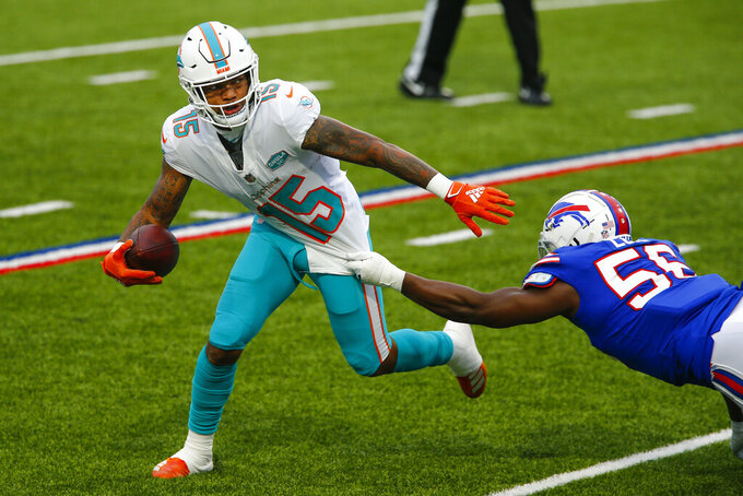 Miami Dolphins wide receiver Lynn Bowden (15) attempts to break a tackle by Buffalo Bills defensive end Mike Love (56) in the first half of an NFL football game, Sunday, Jan. 3, 2021, in Orchard Park, N.Y. (AP Photo/John Munson)