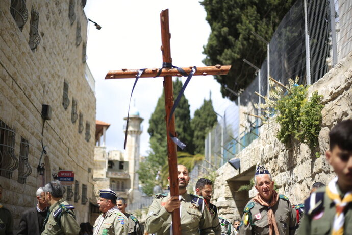 Christian form the boys scouts movement , one carries a cross , walk along the Via Dolorosa towards the Church of the Holy Sepulchre, traditionally believed by many to be the site of the crucifixion of Jesus Christ, during the Good Friday procession in Jerusalem's old city, Friday, April 19, 2019. (AP Photo/Ariel Schalit)