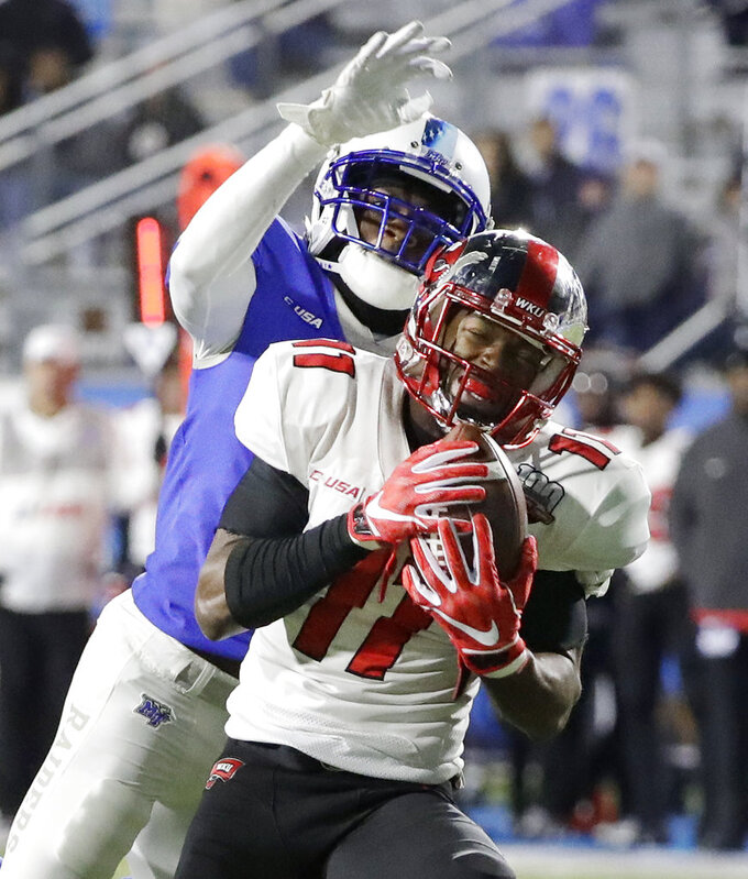 Western Kentucky wide receiver Lucky Jackson (11) catches a 46-yard touchdown pass as he is defended by Middle Tennessee's Chris Stamps during the second half of an NCAA college football game Friday, Nov. 2, 2018, in Murfreesboro, Tenn. Middle Tennessee won 29-10. (AP Photo/Mark Humphrey)