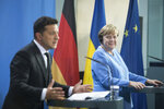 German Chancellor Angela Merkel, right, and Ukrainian President Volodymyr Zelensky give statements ahead of talks at the Chancellery in Berlin, Monday, July 12, 2021. (Stefanie Loos/Pool Photo via AP)