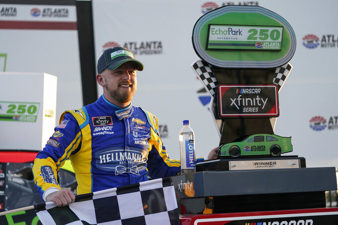 NASCAR driver Justin Allgaier poses with a trophy after he wins a NASCAR Xfinity Series at Atlanta Motor Speedway on Saturday, March 20, 2021, in Hampton, Ga. (AP Photo/Brynn Anderson)