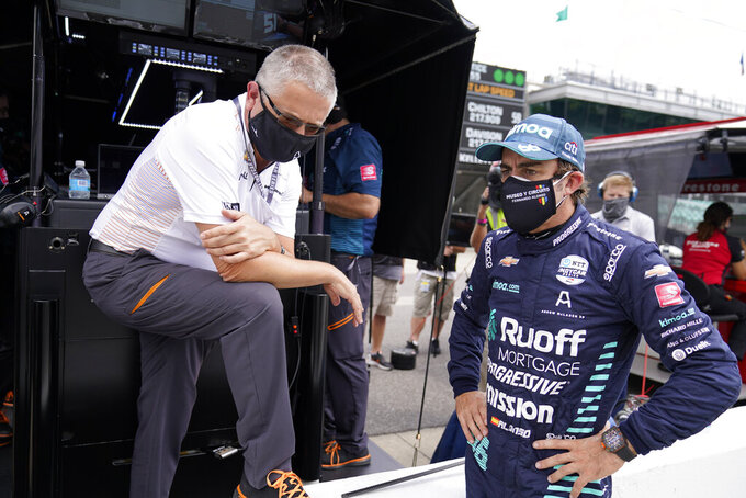 Fernando Alonso, of Spain, talks with Gil de Ferran following a practice session for the Indianapolis 500 auto race at Indianapolis Motor Speedway, Wednesday, Aug. 12, 2020, in Indianapolis. (AP Photo/Darron Cummings)