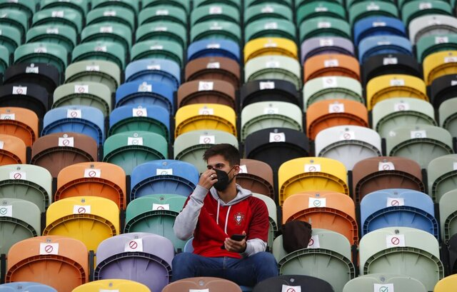 A fan wearing face mask to protect against coronavirus waits for the start of the UEFA Nations League soccer match between Portugal and Sweden at the Jose Alvalade stadium in Lisbon, Portugal, Wednesday, Oct. 14, 2020. (AP Photo/Armando Franca)