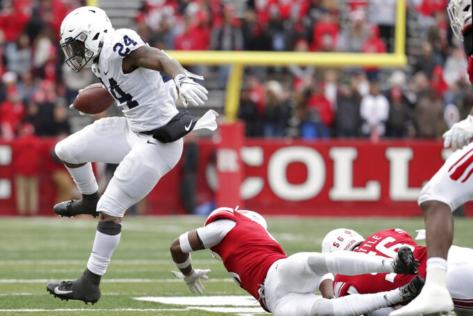 Penn State running back Miles Sanders, left, leaps over Rutgers defenders during the second half of an NCAA college football game, Saturday, Nov. 17, 2018, in Piscataway, N.J. Penn State won 20-7. (AP Photo/Julio Cortez)