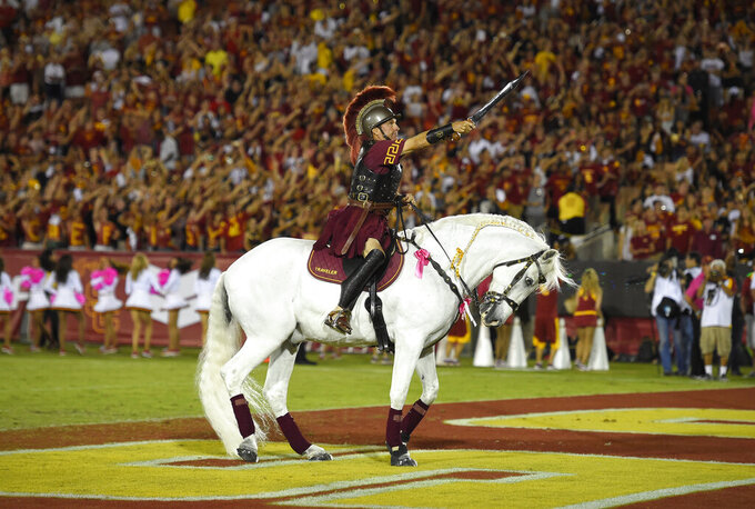 File-Hector Aguilar rides Traveler VII during the second half of an NCAA college football game between Southern California and Utah, Saturday, Oct. 24, 2015, in Los Angeles. Southern Cal's famed white horse, Traveler, won't be galloping triumphantly after a Trojans touchdown. From Ann Arbor to Los Angeles to Oxford, that most American of pursuits, college football,  has either given up hope of getting in a traditional season or is flinging what amounts to a Hail Mary pass in a desperate attempt to hang on in the age of Covid-19.  (AP Photo/Mark J. Terrill, File)