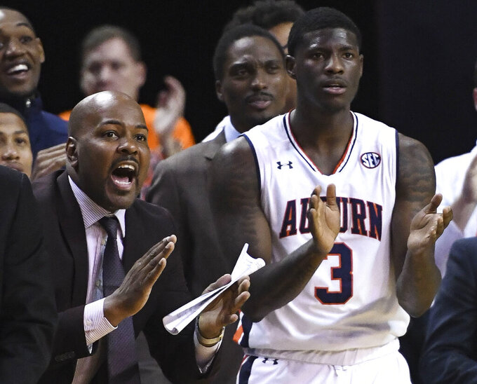 In this Jan. 19, 2019 photo, Auburn assistant coach Ira Bowman, left, cheers from the sidelines during the second half of an NCAA college basketball game against Kentucky in Auburn, Ala. Auburn has suspended Bowman indefinitely on Wednesday, March 3, 2019, amid allegations that he was involved in a bribery scheme during his time at the University of Pennsylvania. (AP Photo/Julie Bennett)