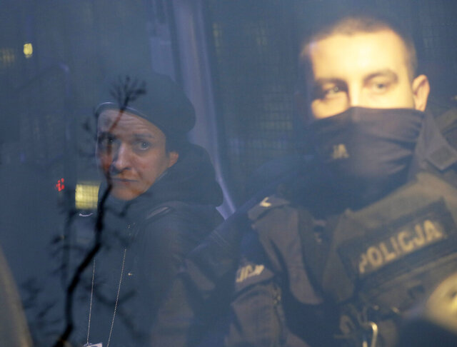 Agata Grzybowska, left, a photo journalist, is detained by police in Warsaw, Poland, on Monday Nov. 23, 2020. Police detained several people as women-led protests over abortion rights flared up again in Warsaw and elsewhere in Poland. The protests, organized by the group Women's Strike, have been occurring regularly ever since the country's constitutional court issued an Oct. 22 ruling that further tightens an abortion law that was already one of the most restrictive in Poland.(AP Photo/Czarek Sokolowski)