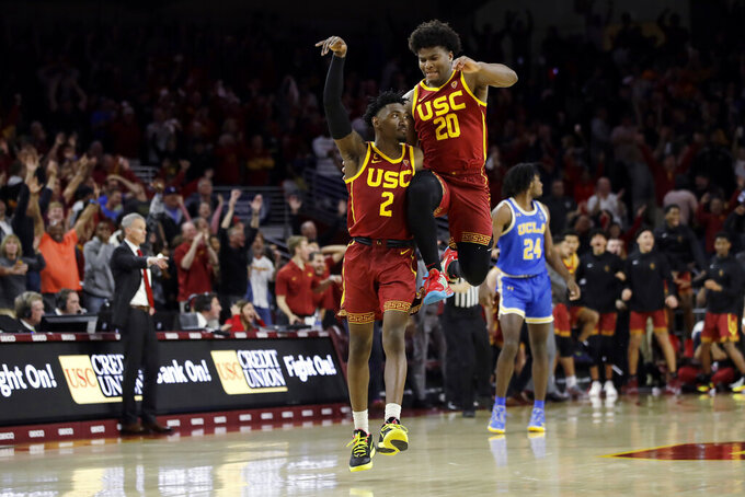 Southern California guard Jonah Mathews (2) celebrates his game-winning 3-point basket with teammate Ethan Anderson (20) in the final seconds of an NCAA college basketball game against UCLA Saturday, March 7, 2020, in Los Angeles. (AP Photo/Marcio Jose Sanchez)