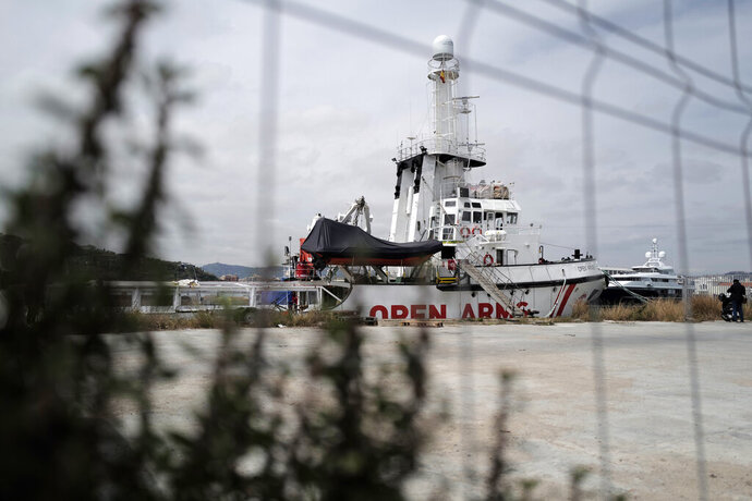 FILE - In this Wednesday April 17, 2019 file photo, The Proactiva's Open Arms rescue boat sits docked in Barcelona, Spain. A judge in Sicily has dropped an investigation against two member of the Spanish aid group Proactiva Open Arms deriving from a tense high-seas standoff last year when the crew refused to hand over 218 migrants rescued at sea to the Libyan coast guard. Proactiva welcomed the decision to drop the investigation into criminal association and aiding illegal migration Wednesday, calling it ''an additional step toward the truth.'' The group stated that it has always operated according to international roles. (AP Photo/Renata Brito)