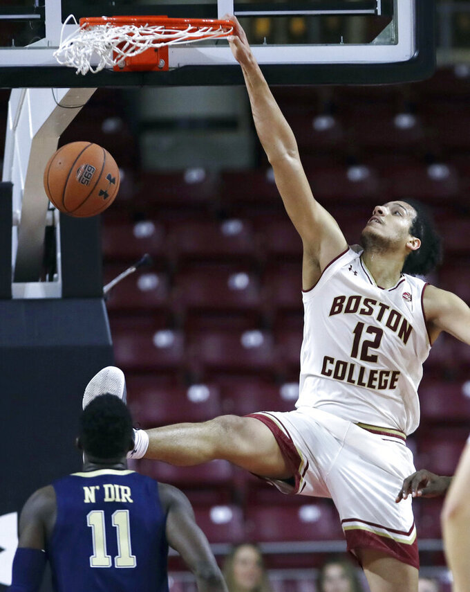 Boston College center Johncarlos Reyes (12) dunks against Pittsburgh guard Sidy N'Dir (11) during the first half of an NCAA college basketball game in Boston, Tuesday, Feb. 12, 2019. (AP Photo/Charles Krupa)