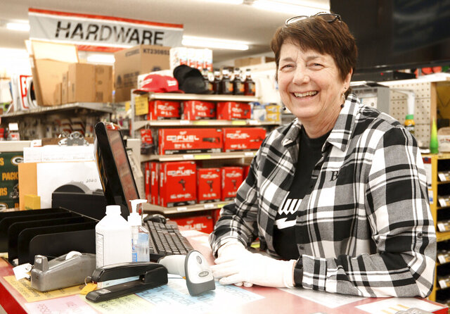 In this Tuesday, March 31, 2020, photo, Rita Parr, owner of Parr's Hardware in Eau Claire, WI., stands behind the counter on. As a COVID-19 precaution, the store recently halved its hours and moved exclusively to curbside orders. (Dan Reiland/The Eau Claire Leader-Telegram via AP)