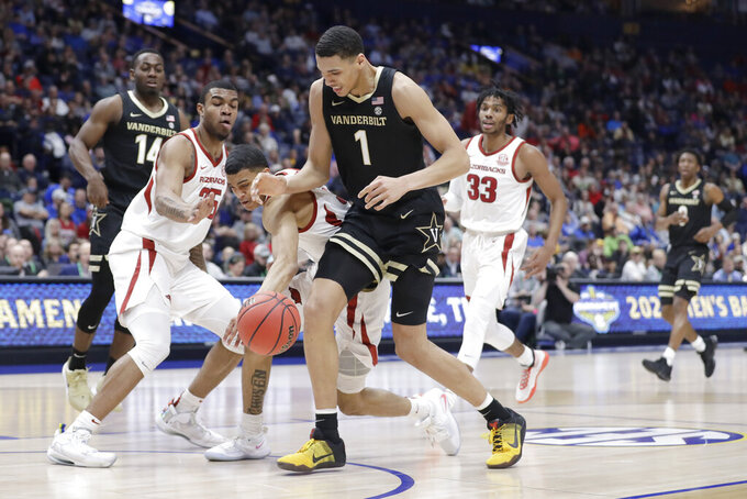 Arkansas guard Jalen Harris, center, knocks the ball away from Vanderbilt forward Dylan Disu (1) in the first half of an NCAA college basketball game in the Southeastern Conference Tournament Wednesday, March 11, 2020, in Nashville, Tenn. (AP Photo/Mark Humphrey)