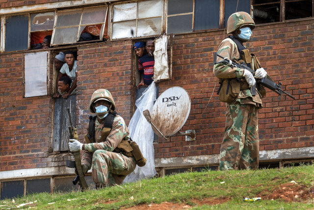 South African National Defense Forces patrol a men's hostel in the densely populated Alexandra township east of Johannesburg, Saturday, March 28, 2020, enforcing a strict lockdown in an effort to control the spread of the coronavirus. Responding quickly with one of the world's harshest lockdowns, South Africa slowed the initial spread of the coronavirus and the country passed its first peak with far less deaths than experts had predicted. (AP Photo/Jerome Delay)