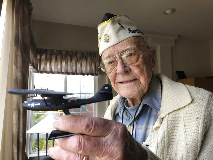 Retired U.S. Navy Cmdr. Don Long holds up a replica of the military seaplane he was standing watch on when Japanese warplanes attacked Hawaii 77 years ago, Friday, Dec. 7, 2018 at his home in Napa, California. Long was alone on the anchored plane in the middle of Kaneohe Bay, across the island from Pearl Harbor, when the attack happened, watching from afar as the bombs and bullets killed and wounded thousands. When the gunfire finally reached his plane, setting the aircraft ablaze, he jumped into the water and found himself swimming through fire to safety. (AP Photo/Eric Risberg)
