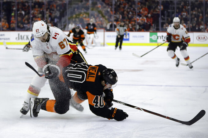 Philadelphia Flyers' Jordan Weal (40) and Calgary Flames' Michael Frolik (67) collide during the second period of an NHL hockey game, Saturday, Jan. 5, 2019, in Philadelphia. (AP Photo/Matt Slocum)