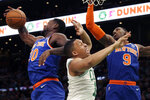 New York Knicks forward Julius Randle (30) gathers in a rebound next to Boston Celtics forward Grant Williams, middle, as Knicks guard RJ Barrett (9) also goes for the ball during the first quarter of an NBA basketball game Friday, Nov. 1, 2019, in Boston. (AP Photo/Elise Amendola)