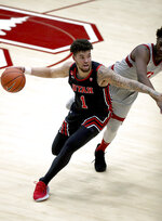 Utah forward Timmy Allen drives around Stanford guard Daejon Davis during the first half of an NCAA college basketball game Saturday, Feb. 13, 2021, in Stanford, Calif. (AP Photo/Scot Tucker)